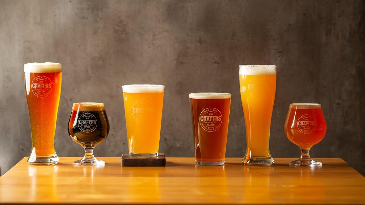 Odlišné druhy piv vyrovnané na stole.