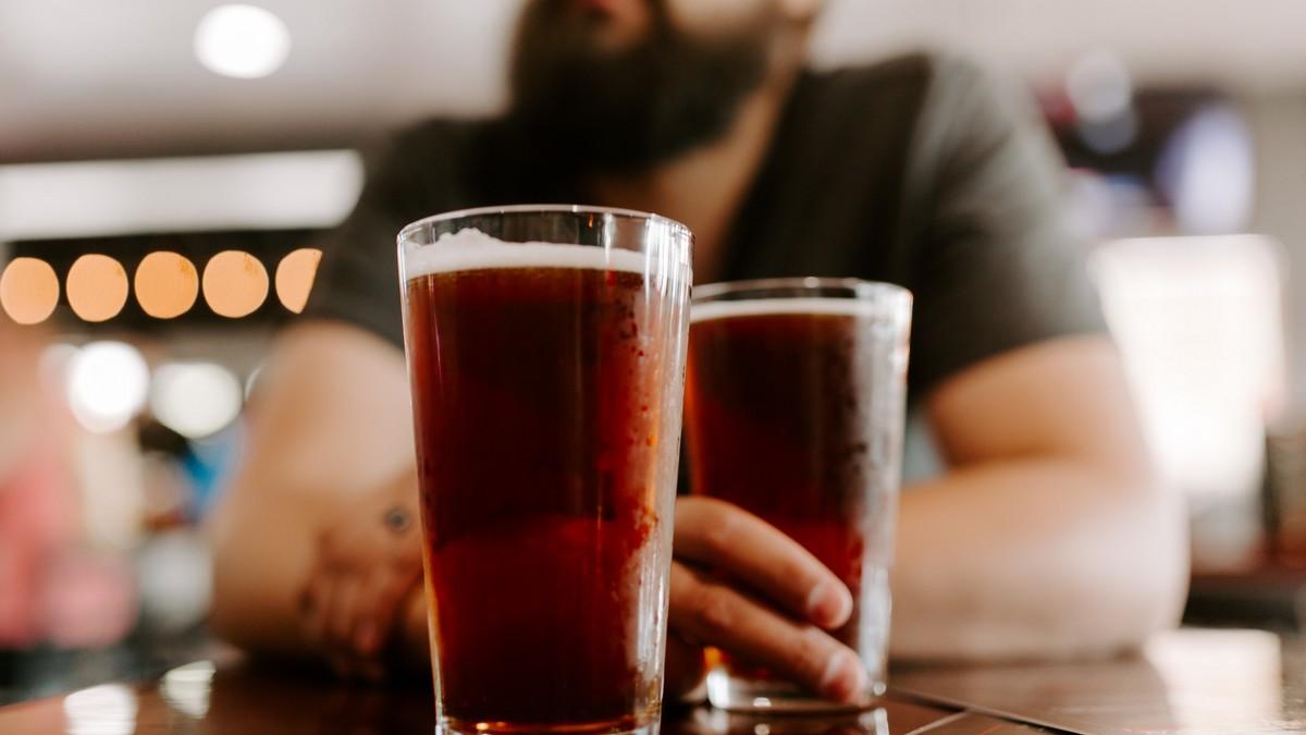 Mladík si v hospodě dopřává nealkoholické pivo.