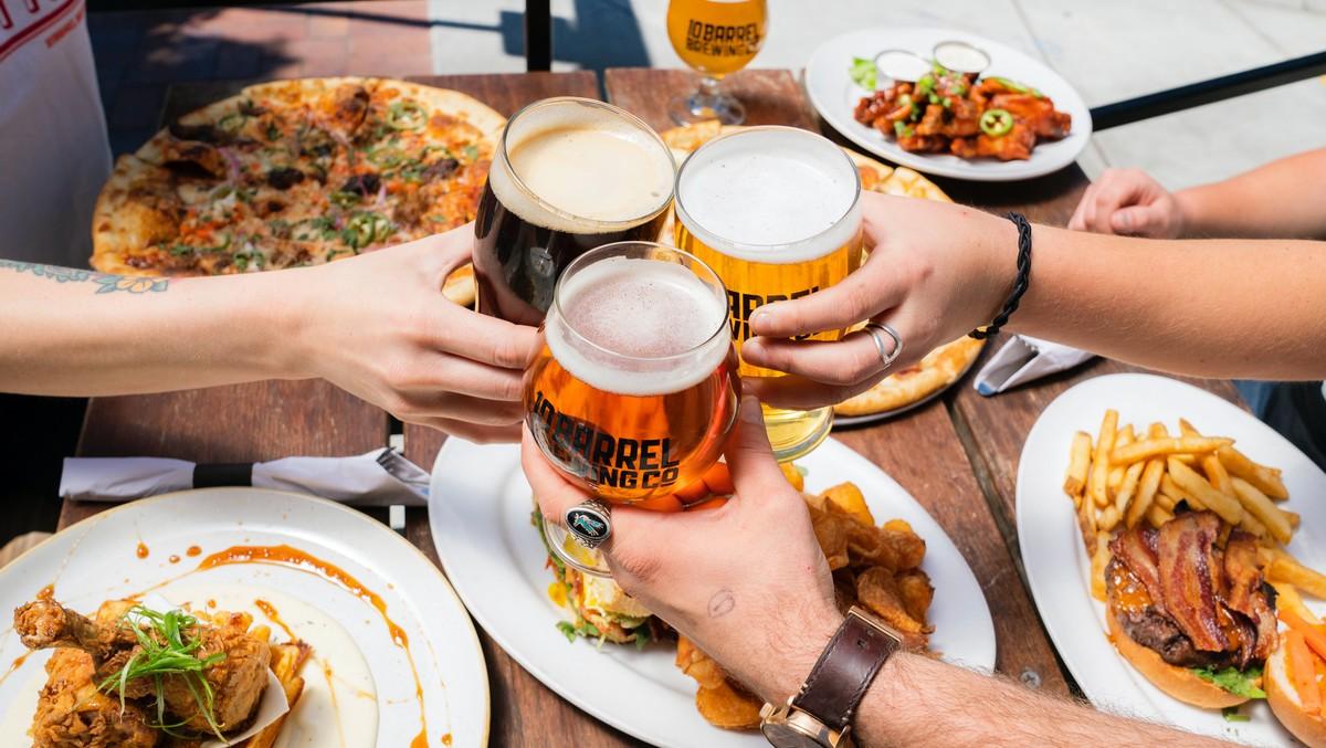 Mladí lidé podporují pivní statistiky a pijí pivo.